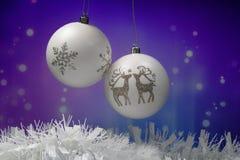 Twee witte Kerstmisballen met sneeuwvlok en rendier voor purpere blauwe achtergrond stock foto