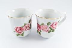 Twee witte koppen van koffie met mooie bloemen Royalty-vrije Stock Foto's