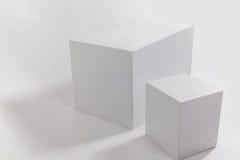 Twee witte kubussen op witte muur Stock Foto's