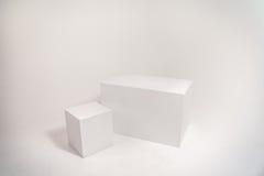 Twee witte kubussen op witte muur Royalty-vrije Stock Afbeeldingen