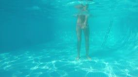 Twee witte meisjes in bikinis ploeteren voor cameralens in blauwe pool Één zit op schouders van een andere Mening van stock video