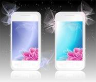 Twee witte mobiele telefoons met bloemenAchtergrond Stock Fotografie