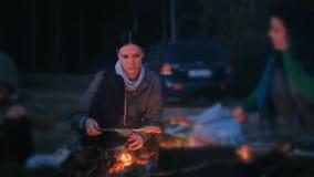 Twee worsten van het vrouwengebraden gerecht op een brand Familie die bij nacht kamperen stock video