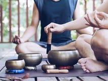 Twee yoga men do yoga openlucht met zingende kommen royalty-vrije stock foto