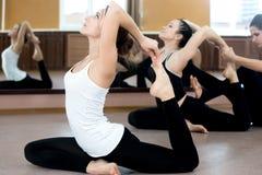 Twee yogiwijfje die in klasse uitoefenen Stock Afbeeldingen