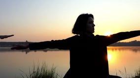 Twee Young Women do Yoga Exercise op de Schitterende Meerbank bij Zonsondergang stock videobeelden