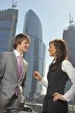 Twee zakenlieden bespreken het project tegen skys Royalty-vrije Stock Afbeeldingen