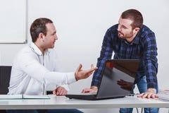 Twee zakenlieden bespreken op vergadering in bureau Stock Afbeelding