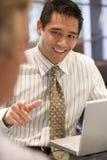 Twee zakenlieden in bestuurskamer met laptop het spreken stock foto's