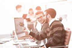 Twee zakenlieden in bureau analyseren toenemende projectstatistieken van laptop het scherm royalty-vrije stock fotografie