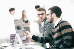 Twee zakenlieden in bureau analyseren toenemende projectstatistieken van laptop het scherm stock fotografie