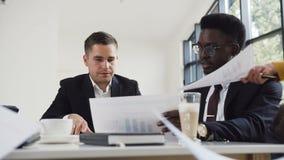 Twee zakenlieden, de afro Amerikaanse en Kaukasische nationaliteit, in bedrijfsjasjes die bij de bureaulijst zitten en bespreken stock videobeelden