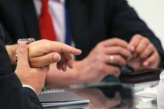 Twee zakenlieden die bij lijst spreken - bespreking over gesprekken royalty-vrije stock afbeeldingen