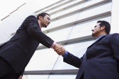 Twee zakenlieden die buiten de bureaubouw samenkomen Stock Foto