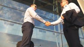 Twee zakenlieden die dichtbij de bureaubouw samenkomen en elkaar begroeten Bedrijfshanddruk openlucht in stedelijk milieu stock videobeelden