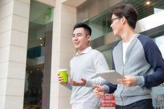 Twee zakenlieden die en in de stad lopen spreken Stock Afbeeldingen