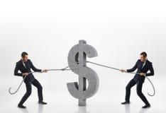 Twee zakenlieden die groot concreet 3d dollarteken met kabels in tegenovergestelde richtingen trekken die op witte achtergrond wo Stock Foto's