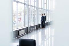 Twee Zakenlieden die Informele Vergadering in Bureaugang hebben stock afbeelding
