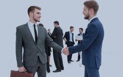 Twee zakenlieden die overeenkomst, hun collega's maken die zich dichtbij bevinden Royalty-vrije Stock Foto's