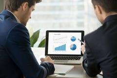 Twee zakenlieden die projectstatistieken van laptop het scherm analyseren royalty-vrije stock fotografie