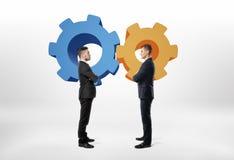 Twee zakenlieden die zich tegengesteld aan elkaar met beeldverhaaltandrad bevinden stock afbeeldingen