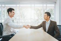 Twee zakenlieden het schudden dient een bureau in royalty-vrije stock afbeelding