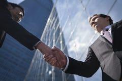 Twee zakenlieden het schudden dient Peking, China, mening van onderaan in Stock Foto's