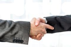 Twee zakenlieden het schudden overhandigt een vage abstracte achtergrond Stock Afbeeldingen
