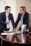 Twee zakenlieden in kostuums die in bestuurskamer werken Royalty-vrije Stock Foto's