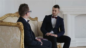 Twee zakenlieden in kostuums met vlinderdassen communiceren in een mooie witte ruimte met elegante gouden bank stock videobeelden