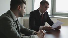 Twee zakenlieden in kostuums zitten bij een lijst voor het venster en leren een nieuw contract stock video
