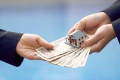 Twee zakenlieden leiden een huisverkoop met een modeldiehuis en Yenbankbiljetten bij 10000 Yen worden getaxeerd het gebruiken als Stock Afbeelding