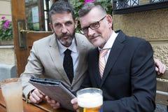 Twee zakenlieden met tablet bij een restaurant stock afbeelding