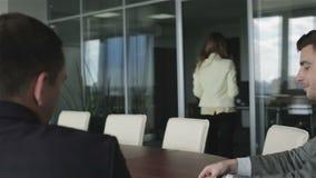 Twee zakenlieden wachten op een nieuw contract in een vergaderingszaal stock video