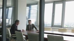 Twee zakenlieden zitten bij een lijst in een ruimte achter een glasmuur stock videobeelden