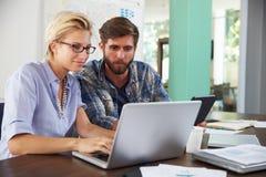 Twee Zakenlui die aan Laptop in Bureau samenwerken Royalty-vrije Stock Afbeeldingen