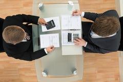 Twee zakenman het berekenen rekeningen die calculator gebruiken Stock Foto