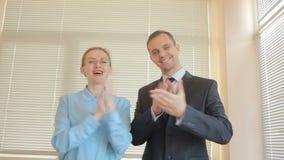 Twee zakenmanman en vrouw die in een bureau op een vensterachtergrond slaan met blinden applaus stock footage