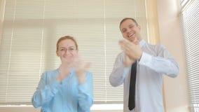 Twee zakenmanman en vrouw die in een bureau op een vensterachtergrond slaan met blinden applaus stock video