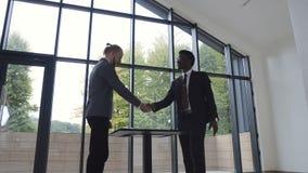 Twee zekere bedrijfsmensen, Afrikaanse Amerikaanse en Kaukasische het schudden handen tijdens een vergadering en het ondertekenen stock videobeelden