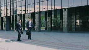 Twee zekere medewerkers die aan het werk op een zonnige ochtend lopen stock videobeelden