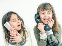 Twee zeven éénjarigenmeisjes die op de oude uitstekende telefoons spreken met Stock Foto's