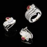 Twee zilveren oorringen en robijnrode ring Royalty-vrije Stock Afbeeldingen