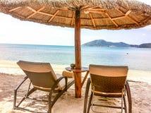 Twee zitkamerstoelen en een strandtent op het strand stock foto