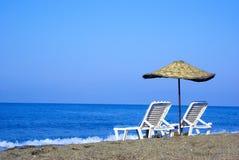 Twee zitkamerstoelen en parasol op het strand Stock Afbeeldingen