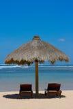 Twee zitkamerstoelen onder tent op strand Stock Foto