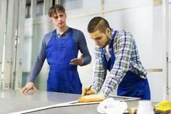 Twee zorgvuldige werklieden die glas snijden Stock Fotografie