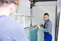 Twee zorgvuldige werklieden die met glas werken Stock Foto's