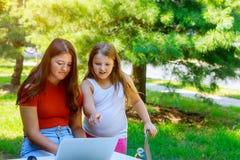 twee zusterontspanning aan gelukkig spelnotitieboekje in openlucht zonnige dag Royalty-vrije Stock Foto's