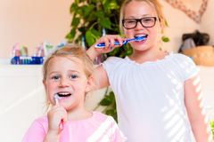 Twee zusters in badkamers het borstelen tanden Stock Afbeelding